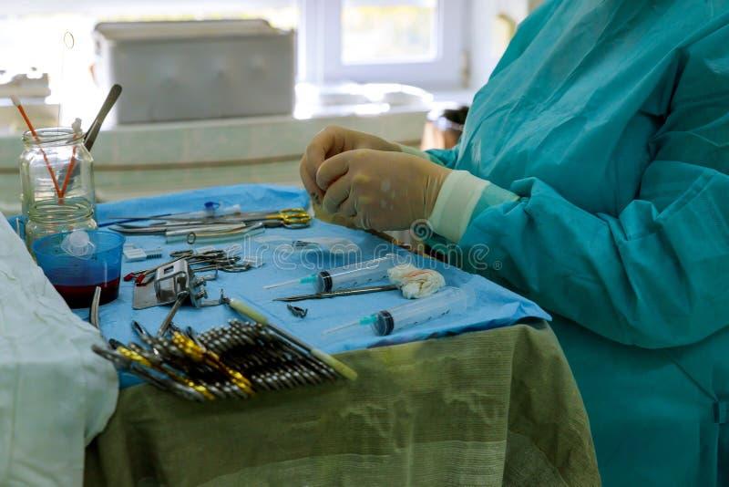 Chirurgiehulpmiddelen op lijst met arts op achtergrond stock foto