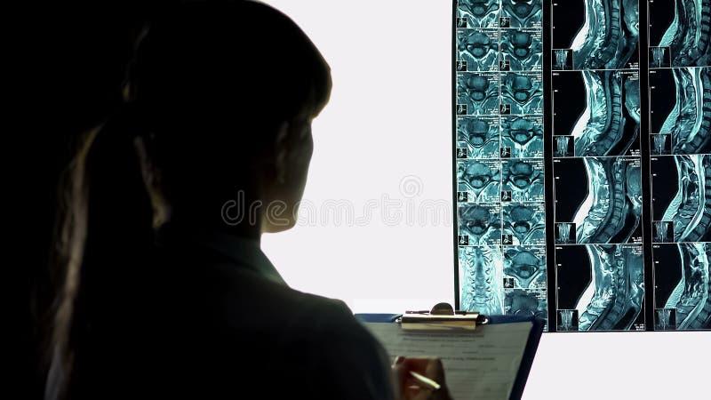 Chirurgien analysant le rayon X de patients et notant le diagnostic dans les disques médicaux images stock