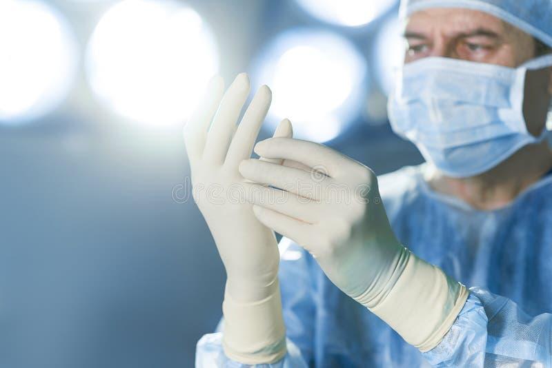 Chirurgien concentré habillé dans l'uniforme protecteur photo libre de droits