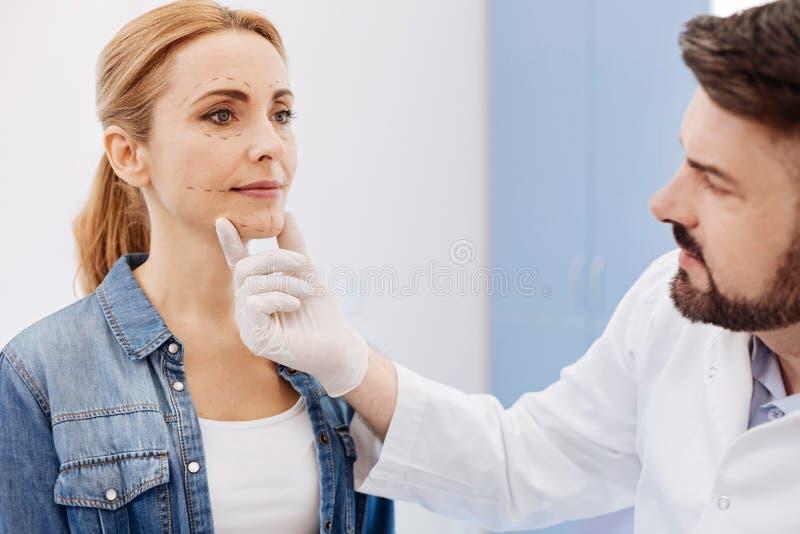 Chirurgien cosmétique sérieux tenant son menton de patients photos stock