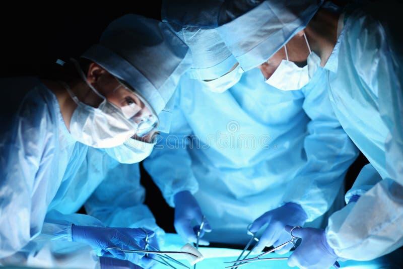 Chirurgien d'équipe au travail dans la salle d'opération images libres de droits