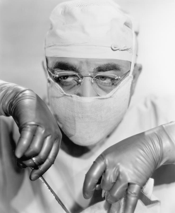 Chirurgien dans une opération de masque chirurgical (toutes les personnes représentées ne sont pas plus long vivantes et aucun do images libres de droits
