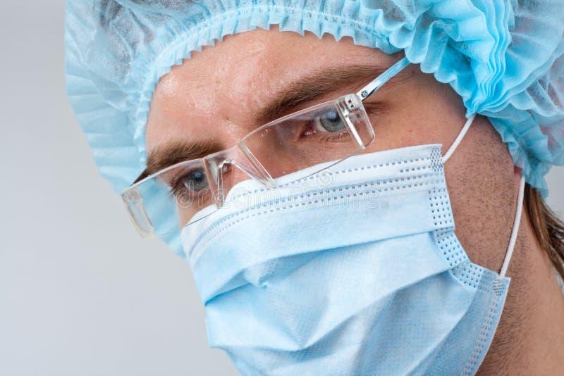 Chirurgien de sueur dans le masque chirurgical photos libres de droits