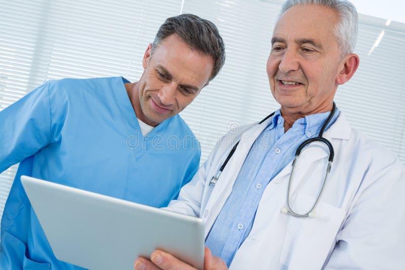 Chirurgien et docteur discutant au-dessus du comprimé numérique photographie stock libre de droits