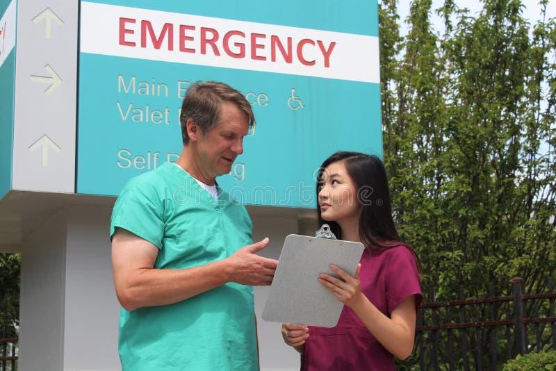 Chirurgien, médecin, médecin, clinicien et infirmière asiatique Wearing Scrubs Stand devant le signe de chambre de secours d'hôpi images libres de droits