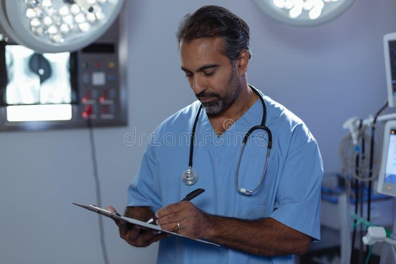 Chirurgien masculin mûr écrivant sur la pièce en fonction de presse-papiers à l'hôpital image stock
