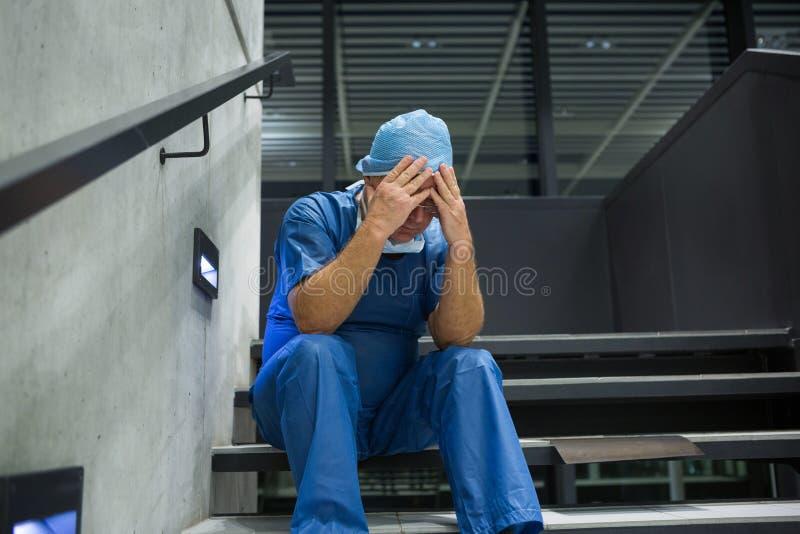 Chirurgien masculin tendu s'asseyant avec des mains sur le front sur l'escalier photos stock