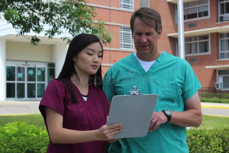 Chirurgien ou médecin ou médecin ou clinicien et infirmière asiatique Stand devant l'hôpital discutant le diagramme patient image stock