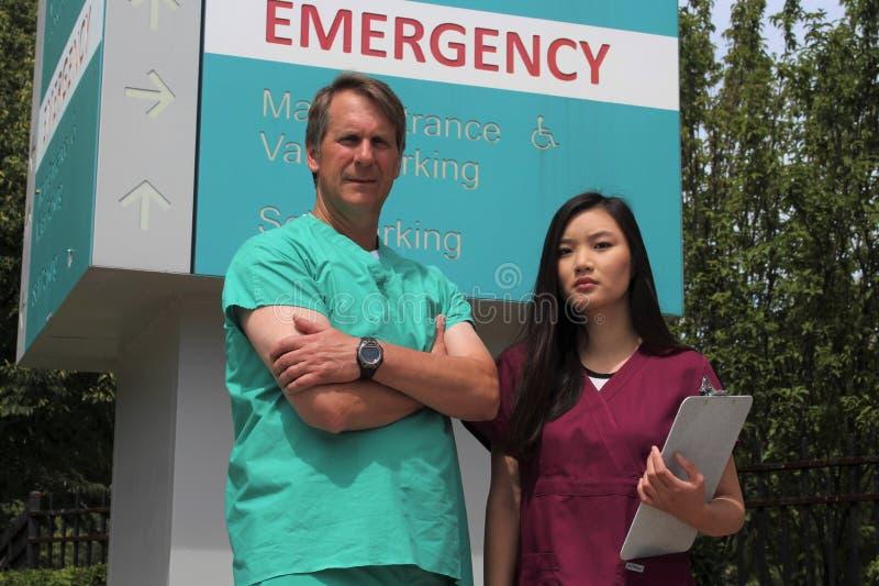 Chirurgien ou médecin ou médecin ou clinicien et infirmière asiatique Stand devant le signe de chambre de secours d'hôpital image libre de droits