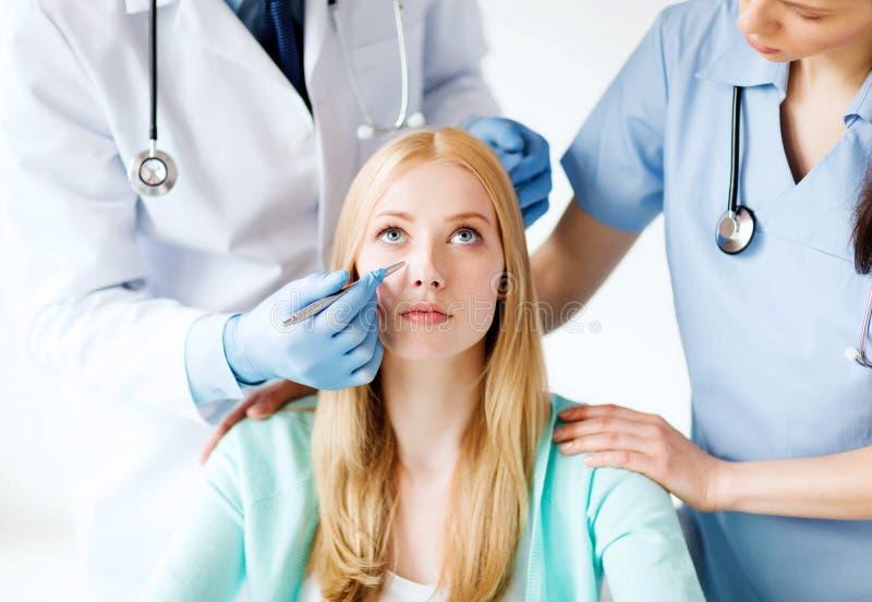 Chirurgien plasticien et infirmière avec le patient photographie stock libre de droits