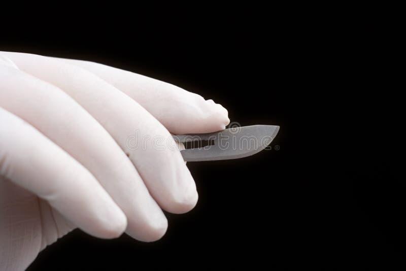 Chirurgien retenant une lame photos stock