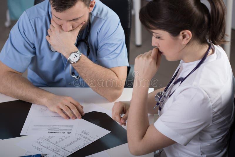 Chirurgiens analysant la documentation clinique patiente image stock