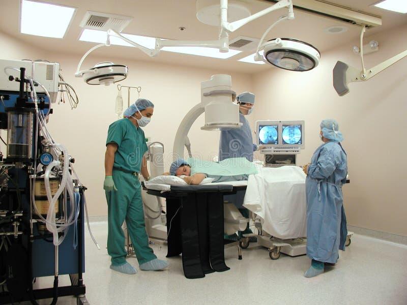 Chirurgiens avec le bras de C dans la salle d'opération image libre de droits