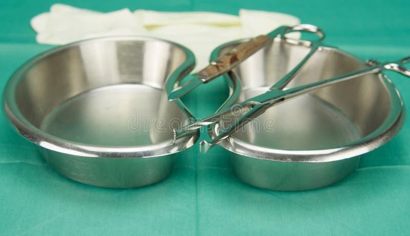 Chirurgisch die klem en mes op de roestvrije kom van de niervorm wordt geplaatst stock foto's