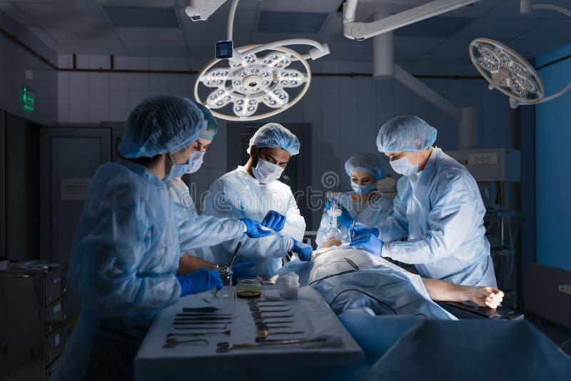 Chirurgische hulpmiddelen die op lijst met verpleegster dichtbijgelegen en chirurgen liggen bij achtergrond royalty-vrije stock afbeeldingen
