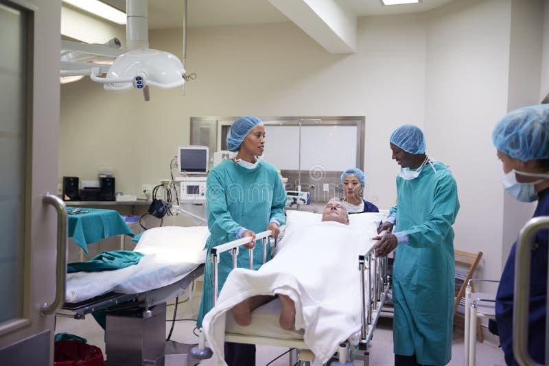 Chirurgischer Team Wheeling Senior Male Patient aus Krankenhaus-Funktionierentheater heraus stockbild