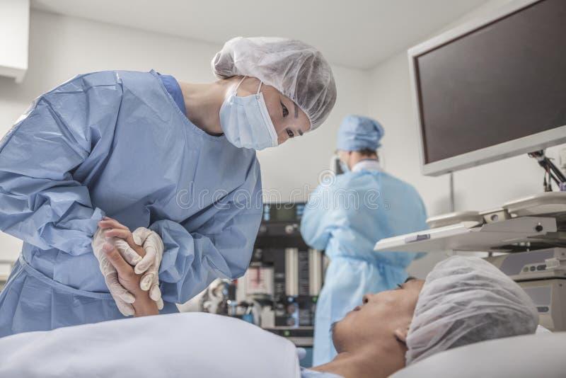 Chirurgo che consulta un paziente, tenendosi per mano, preparantesi per la chirurgia fotografia stock libera da diritti