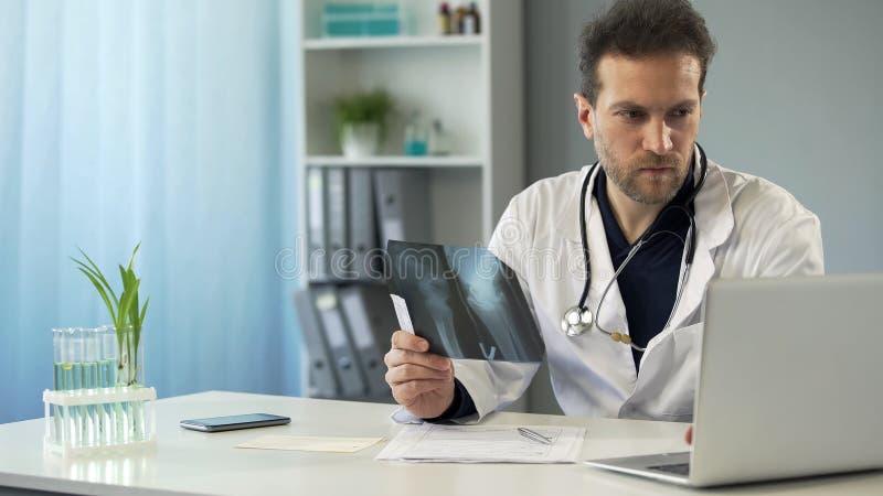 Chirurgo che studia raggi x dell'osso e che fa prescrizione in carta online sul computer portatile immagine stock libera da diritti