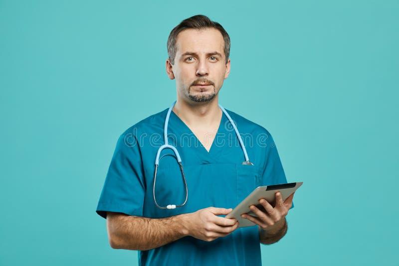 Chirurgo che utilizza una tavoletta digitale sul posto di lavoro fotografie stock libere da diritti