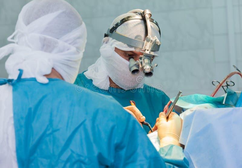 Chirurgo con la lente durante l'operazione fotografie stock libere da diritti