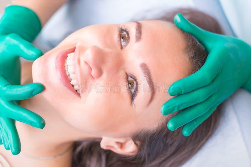 Chirurgo cosmetico che esamina cliente femminile nel clinik prima del plast fotografia stock
