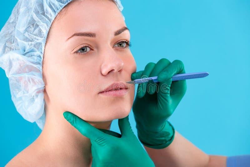 Chirurgo cosmetico Examining Female Client in ufficio Medico che controlla il fronte della donna, la palpebra prima di chirurgia  immagine stock