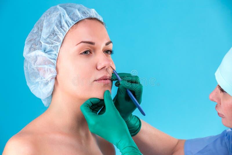 Chirurgo cosmetico Examining Female Client in ufficio Medico che controlla il fronte della donna, la palpebra prima di chirurgia  fotografie stock