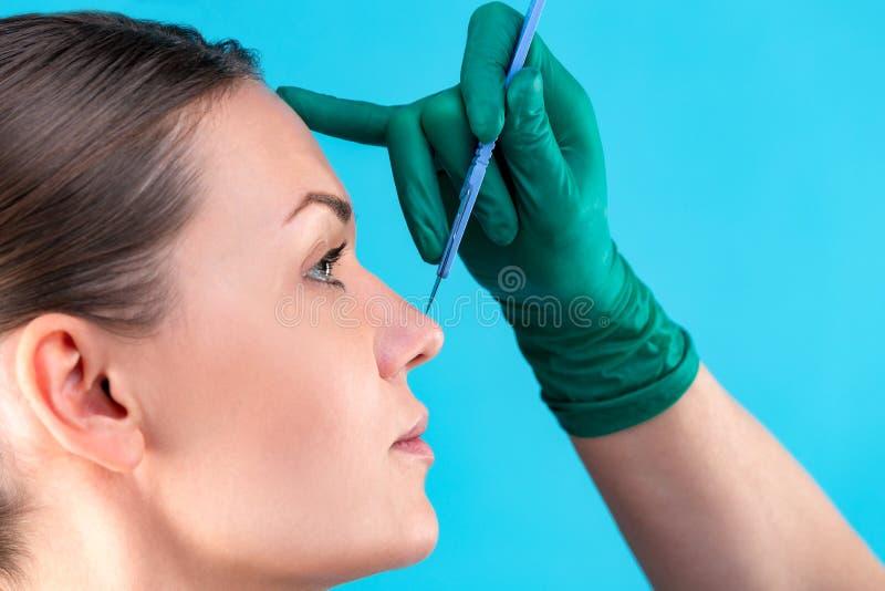 Chirurgo cosmetico Examining Female Client in ufficio Medico che controlla il fronte della donna, il naso prima di chirurgia plas fotografia stock