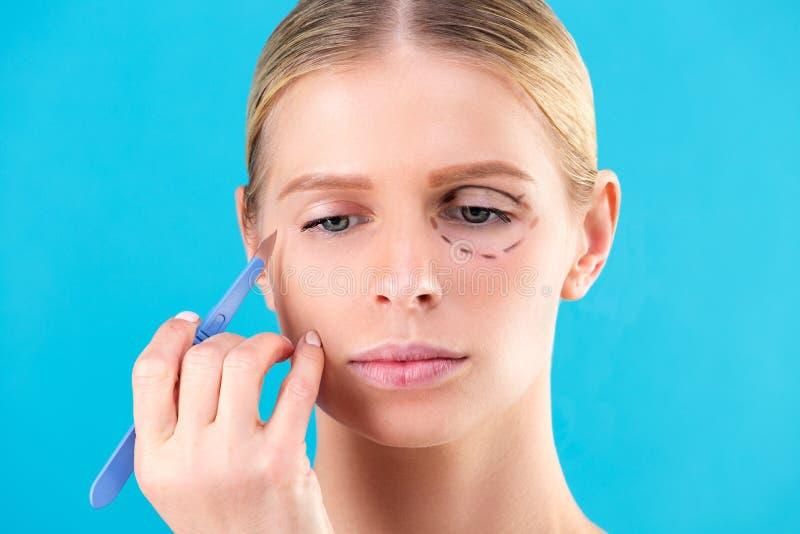 Chirurgo cosmetico Examining Female Client in ufficio Medico disegna le linee con un indicatore, la palpebra prima di chirurgia p fotografie stock