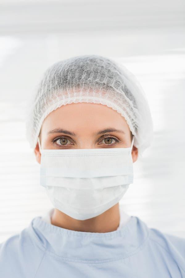 Chirurgo femminile che indossa cappuccio e maschera chirurgici immagine stock