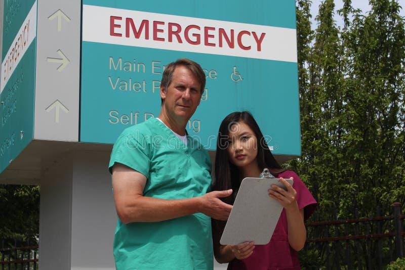 Chirurgo, medico, medico, clinico ed infermiere asiatico Wearing Scrubs Stand davanti al segno del pronto soccorso dell'ospedale immagine stock libera da diritti