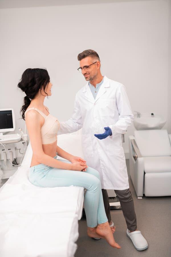 Chirurgo plastico barbuto che parla con cliente dopo l'impianto del silicone fotografia stock libera da diritti