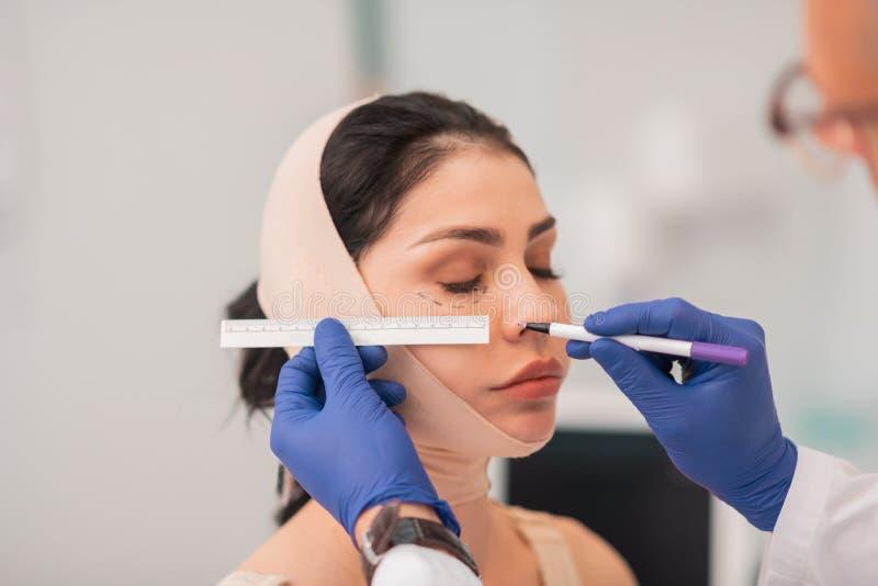Chirurgo plastico che indossa i guanti blu che effettuano le misure del fronte immagine stock