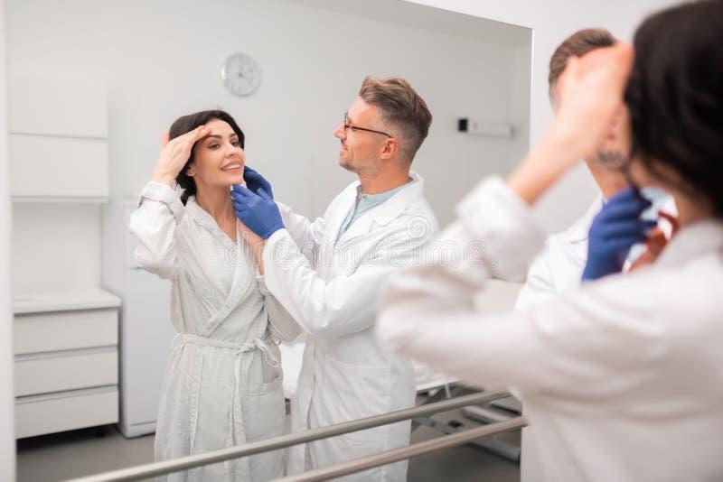 Chirurgo plastico e cliente che esaminano specchio dopo la chirurgia immagini stock libere da diritti