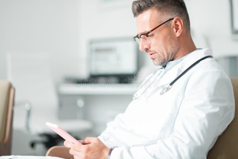Chirurgo plastico professionista che per mezzo della compressa mentre fissando le riunioni fotografia stock
