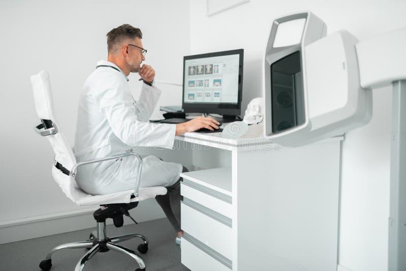 Chirurgo plastico professionista che si siede al computer mentre lavorando fotografia stock libera da diritti
