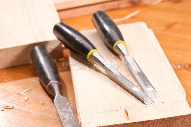 Chisel. Tools series: steel chisel on wooden plank with shaving stock photo