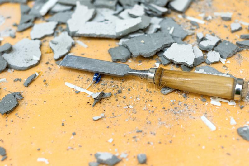 The chisel lies in the middle of pieces of cement and plaster. Dirty, littered workplace royalty free stock images
