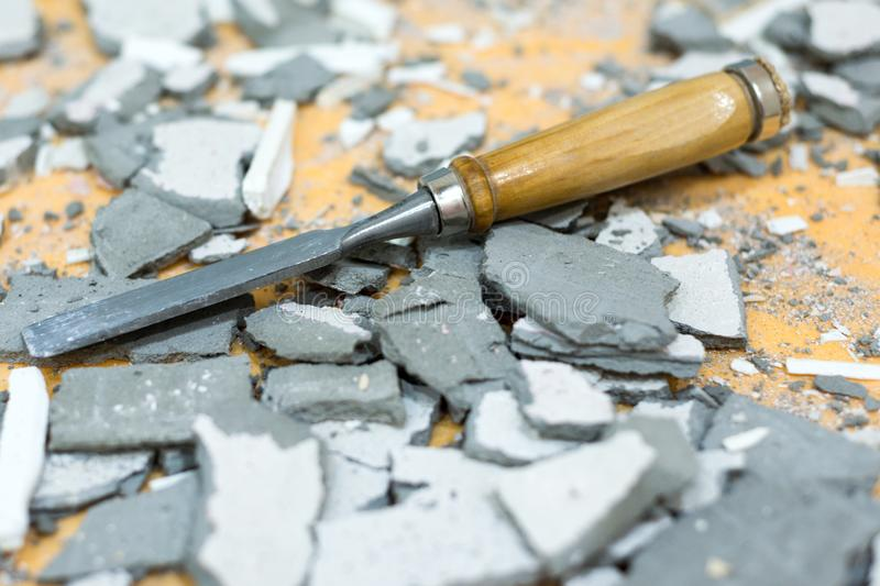 The chisel lies in the middle of pieces of cement and plaster. Dirty, littered workplace stock photo