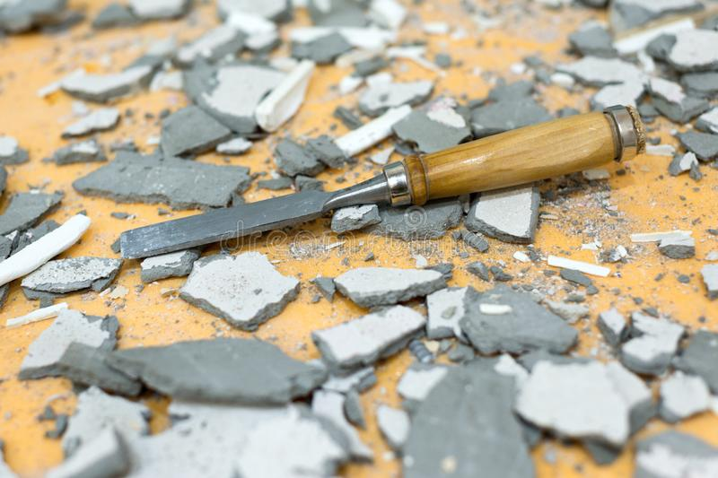 The chisel lies in the middle of pieces of cement and plaster. Dirty, littered workplace stock photography