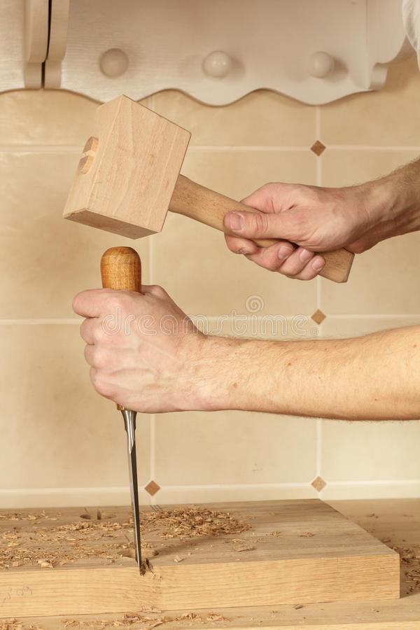 Chisel and mallet in hands. Carpenter working with chisel and mallet making a countertop joint royalty free stock images