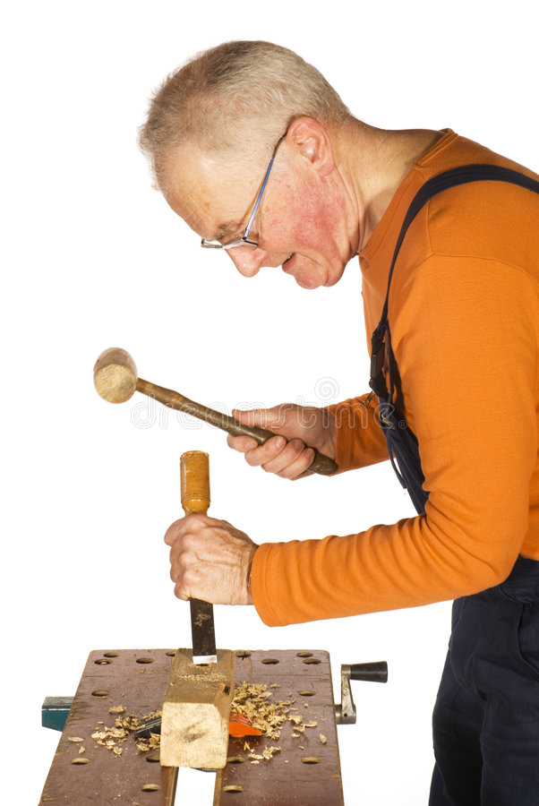 Chiseling and carving the wood. Carpenter is chiseling and carving the wood stock photo