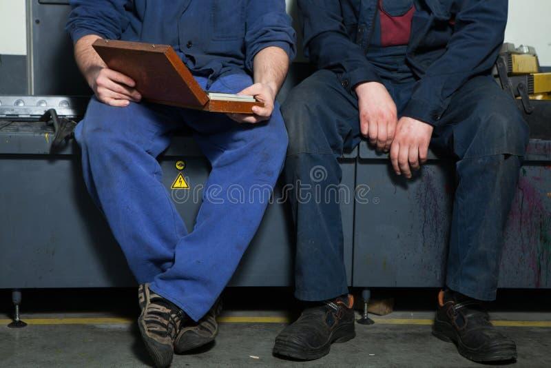 CHISINAU, EL MOLDAVIA - 26 DE ABRIL DE 2016: Trabajadores en casa de impresión Gente que trabaja en la impresora en fábrica de la imagen de archivo