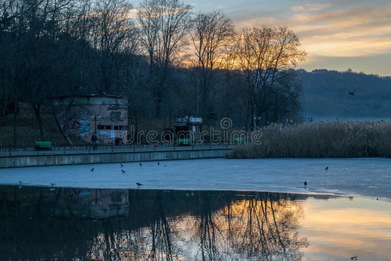 CHISINAU, EL MOLDAVIA - 26 DE DICIEMBRE DE 2016: Vista al lago durante amanecer con un poco de hielo en él fotos de archivo libres de regalías