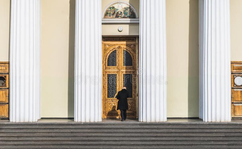 CHISINAU, MOLDOVA - 5 DE FEVEREIRO DE 2016: Um homem não identificado que entra na catedral de chisinau no centro do ce da cidade imagem de stock