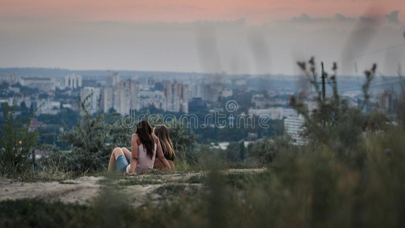 CHISINAU, MOLDOVA - 17 JULY, 2016: Two girls standing on hill watching the sunset in Chisinau royalty free stock images