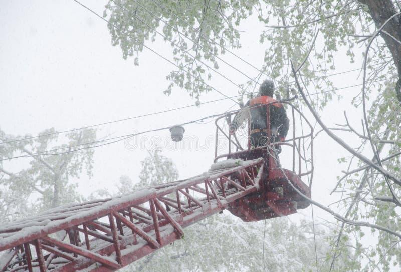 Chisinau, Repubblica di Moldavia - 20 aprile 2017: L'elettricista resta sul palo della torre e ripara un cavo della linea elettri fotografie stock