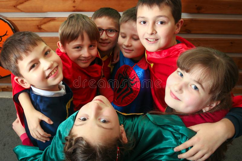 Chisinau, Republic of Moldova - December 12, 2017: A group of kids in superhero costumes are playing and hugging. Look up. stock photography