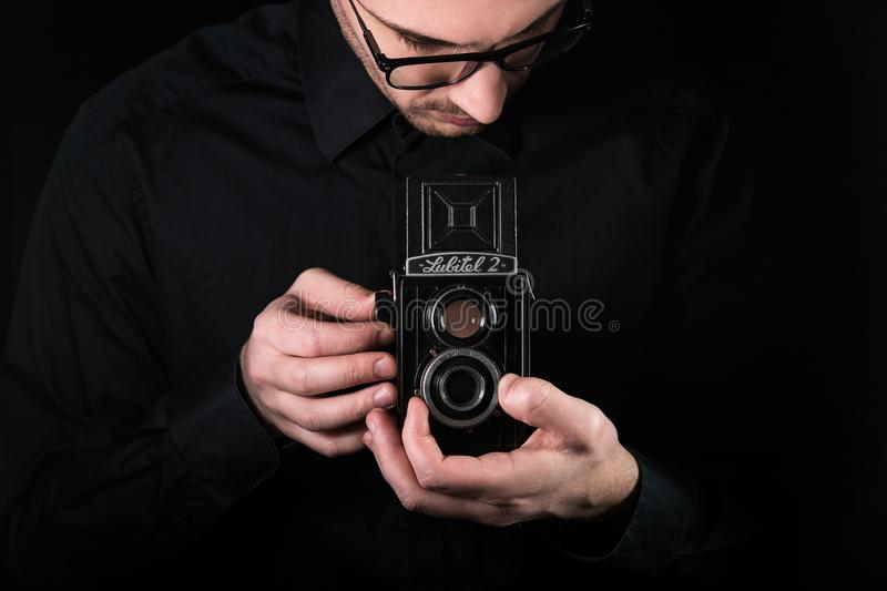 Chisinau, Republic of Moldova - March 12, 2019: A man photographer holds the retro photo camera Lubitel-2, medium format twin-lens. Reflex camera manufactured royalty free stock photos