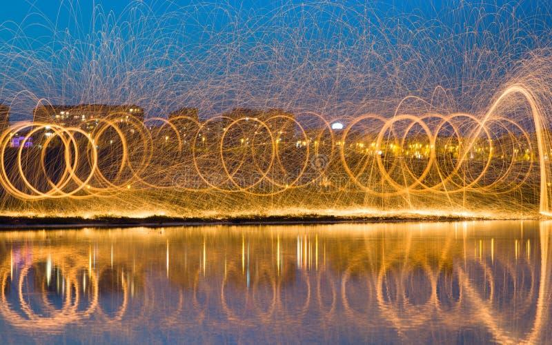 Chispas de oro calientes que vuelan de las lanas de acero ardientes de giro del hombre fotografía de archivo libre de regalías